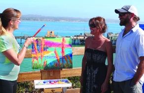 Art lovers Marla and Brad, visiting from Gulfport, Florida, meet Santa Cruz artist Maggie Renner Hellman as she paints en plein air. Photo by Ron Holman.